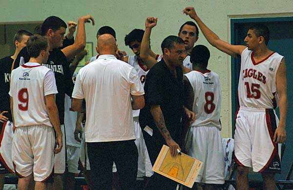 The Kwantlen Eagles convene and listen to head coach Bernie Love during a time-out.