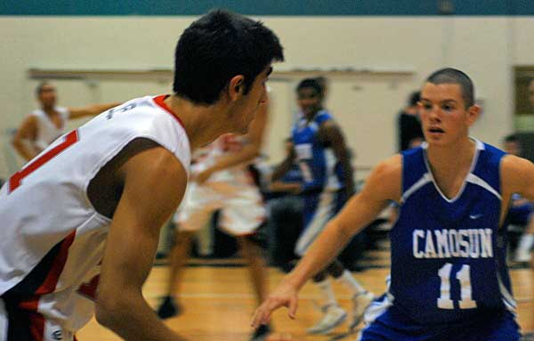 Guard Omid Davani dribbles the ball up the court before being challenged by Kamal Vaid, a forward for the Camosun Chargers.