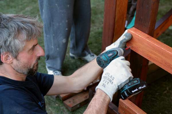 Keefer secures the ladder that will lead up to a new wooden playhouse for the children. The house was donated to the family by Home Depot. (Mitch Thompson photo)