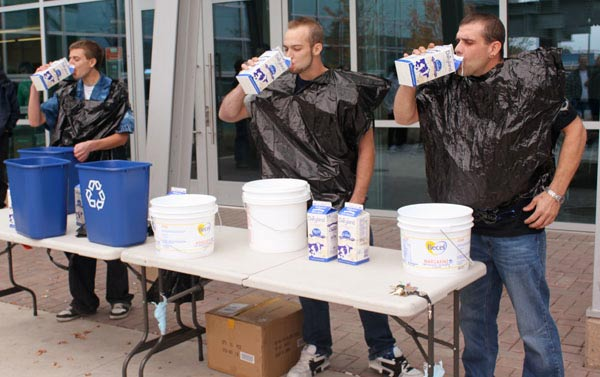 While drinking milk as fast as they could, Mike Kloeble, Jeremy Johnson and Bryan Barker wore garbage bags to keep from spilling on themselves. (Jacob Zinn photo)