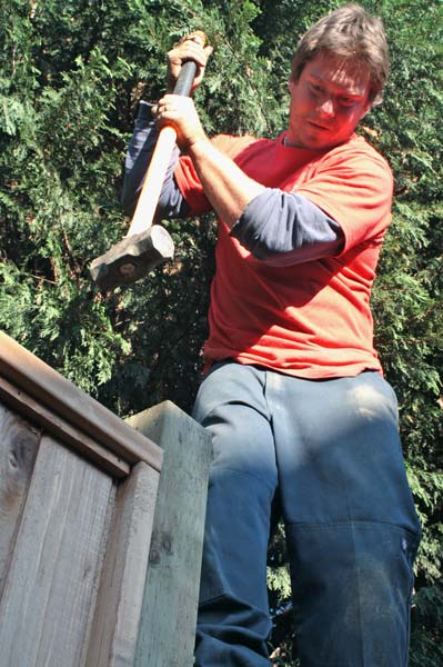 Adam Graham lends a hand to the carpenter by hammering the final section of fence into place. (Mitch Thompson photo)