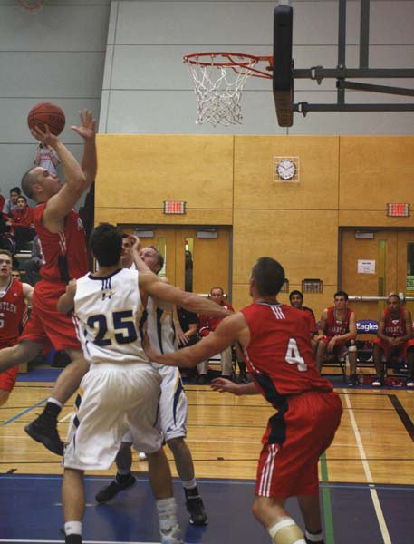 Kwantlen's Kenny Ryan (left) goes up for a shot. He was later ejected from the game for hitting a UBCO player under the net.