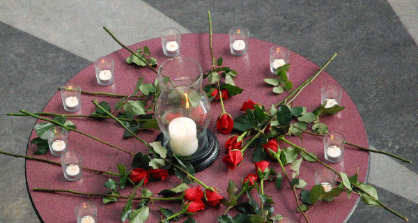 Fourteen roses and candles on a tabletop in the Richmond rotunda as a small gathering of students remembered. (Kim Ytsma photo)