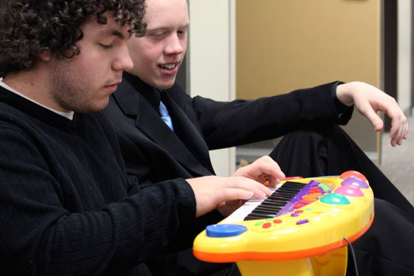 "Alto sax student Laurence Cain, 18, watches guitar student Kyle Poehlke, 21, plays ""A Thousand Miles"" by Vanessa Carlton on a vintage Fisher Price toy piano. (Jacob Zinn photo)"