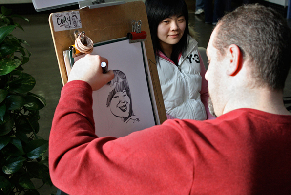 Kwantlen alumni Cory Van Ieperen of Corycatures puts the finishing touches on a portrait of a current student. (Kyle Vinoly Photo)
