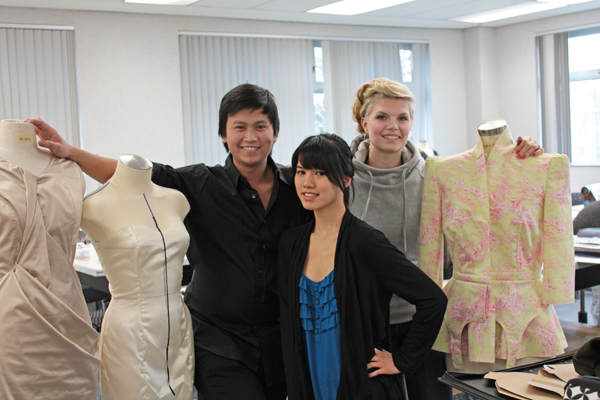 Fashion students pose with some of their work