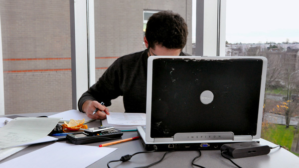 guy hiding behind laptop